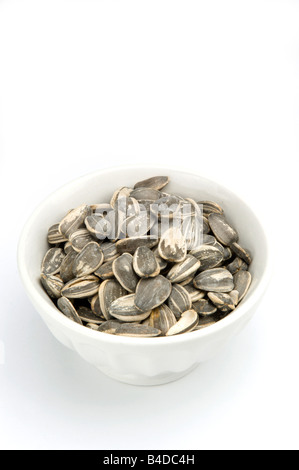 Sunflower seeds in shell in white bowl on white - Stock Photo