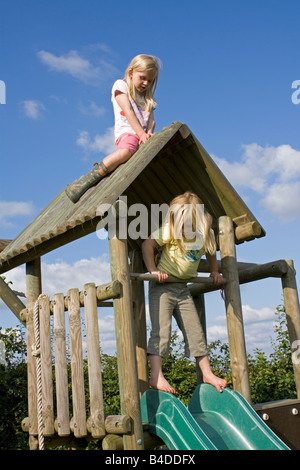 Children playing on play equipment climbing frame in garden young child on roof and younger child on slide - Stock Photo