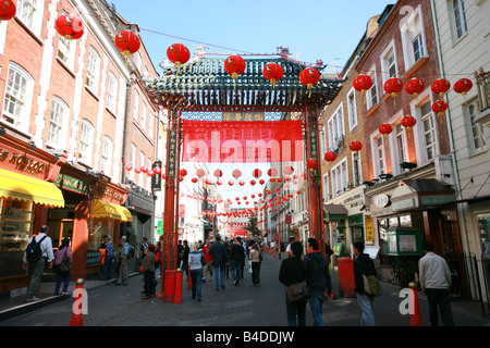 Tourists pass under the main red gateway entrance to China Town in London's West End area England UK - Stock Photo