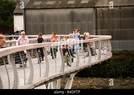 UK Yorkshire Castleford Grand Designs Big Town Plan children on bikes crossing new footbridge over River Aire - Stock Photo