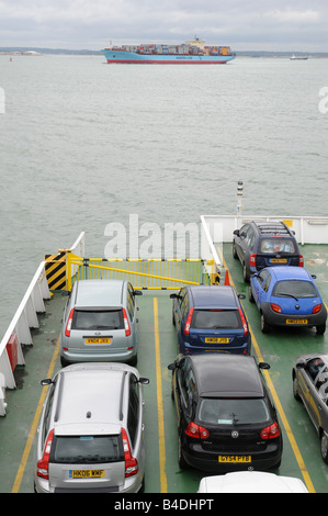 Red Funnel Car Ferry with Container ship crossing in front - Stock Photo