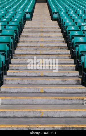 Numbered steps in a sports stadium in between the green pastic seating - Stock Photo