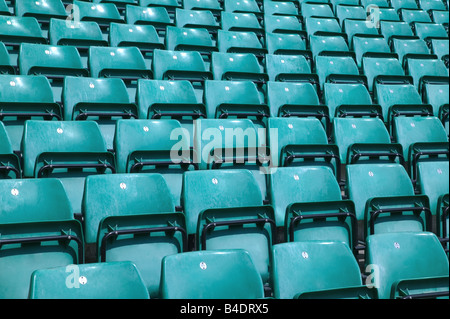 Rows of empty green plastic chairs in a sports stadium - Stock Photo
