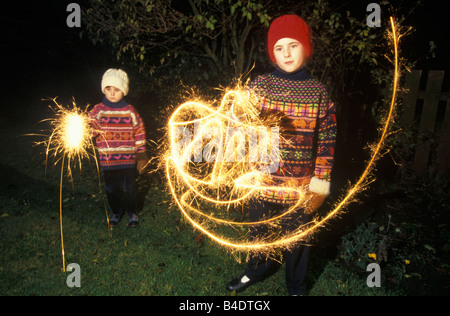 2 girls playing with sparklers on bonfire night - Stock Photo