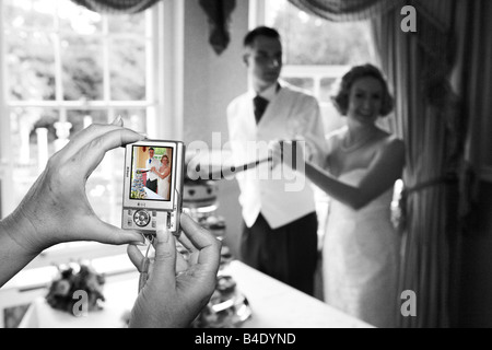 Bride and Groom cut wedding cake on their wedding day photographed by guest using digital camera unusual different - Stock Photo