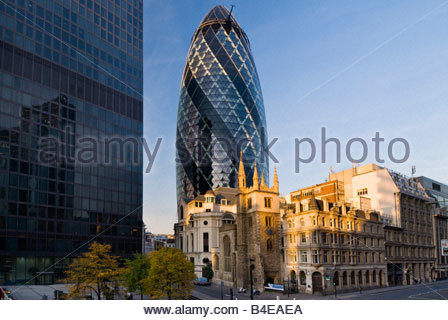 30 St Mary Axe, known as The Gherkin, with St Andrew Undershaft church in the foreground, The City of London, England, - Stock Photo