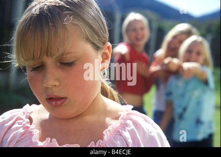 plump little girl being teased by other girls - Stock Photo