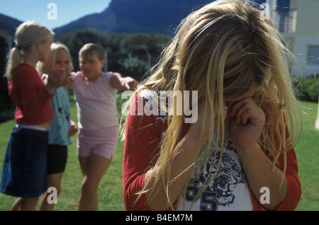 little girl being teased and bullied by other girls - Stock Photo