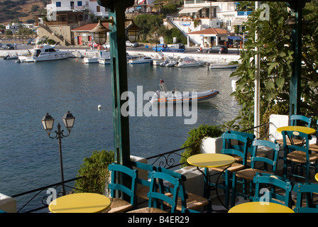Empty Tables and Chairs in Taverna Overlooking Batsi Town and Harbour isle of Andros Cyclades Islands Greece - Stock Photo