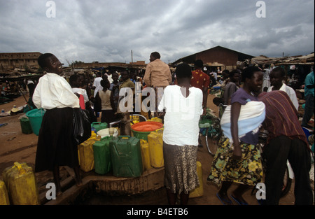 Villagers filling water from pump in village, Uganda - Stock Photo