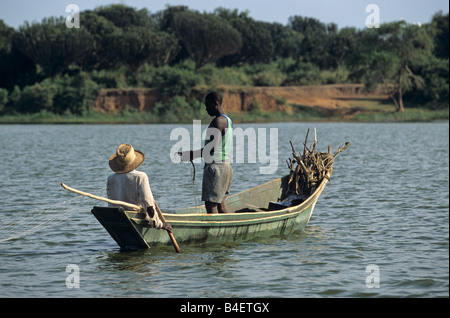 Local fishermen casting net from boat afloat calm lake. Uganda.