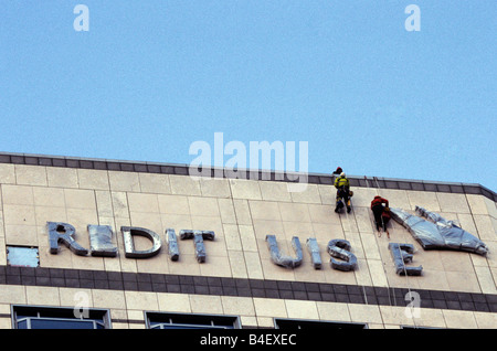 Rope suspended cleaners on a high office building at Canary Wharf in London. - Stock Photo