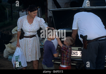 White family in South Africa, with adults having guns on themselves for protection. - Stock Photo