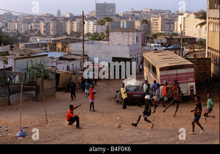 Young men playing football on city wasteland, Luanda, Angola, Africa. - Stock Photo