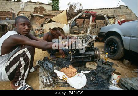 Mechanics working on car engine, dumped car in background, Angola - Stock Photo