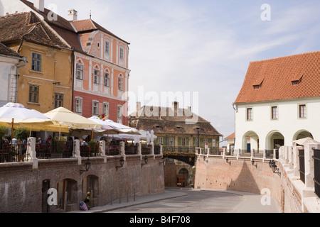 Sibiu Transylvania Romania ld buildings and street under Liars Bridge in Piata Mica small square in historic city - Stock Photo