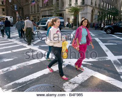 Shoppers on Fifth Avenue in Manhattan New York crossing the street - Stock Photo