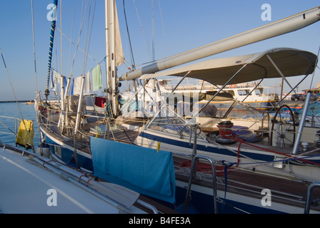 Washing Hanging Out to Dry in Early Morning Sunshine on Yachts at Tinos Town Harbour Cyclades Islands Aegean Sea - Stock Photo