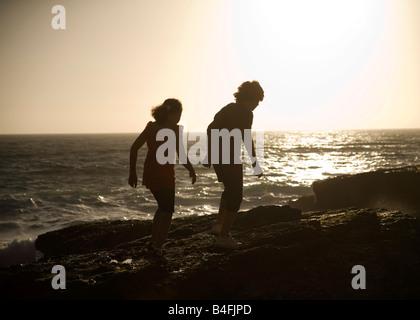 A boy and girl walk up to a cliff edge by the ocean in Santa Cruz California - Stock Photo