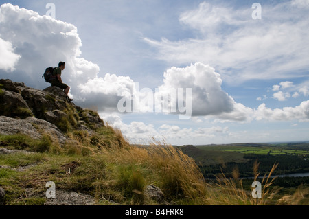 A Soldier on top of Leather Tor on Dartmoor looking out over Burrator Reservoir - Stock Photo