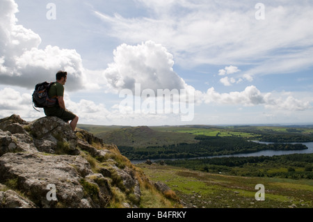 A Walker on top of Leather Tor on Dartmoor looking out over Burrator Reservoir - Stock Photo