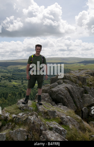 A Hiker on top of Leather Tor on Dartmoor looking out over Burrator Reservoir - Stock Photo