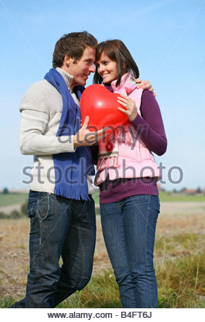 young couple standing the landscape, man giving his girl friend a heart-shaped red balloon - Stock Photo