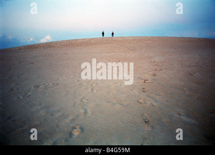 Two people on a dune in the Slowinski National Park in Leba, Poland - Stock Photo