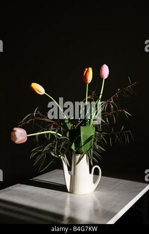 A bouquet of tulips in a watering can on a table, still life - Stock Photo