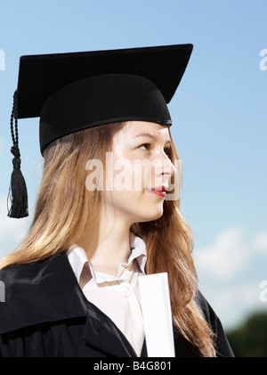A female graduate holding a diploma - Stock Photo