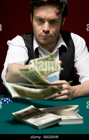 A man throwing money into the pot at a high stakes poker game - Stock Photo