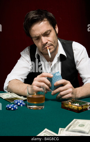 A man at a high stakes poker game looking at his hand of cards - Stock Photo