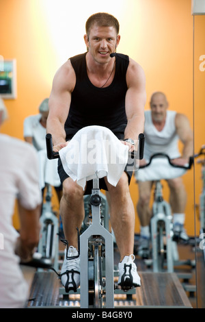 A fitness instructor on a stationary bike teaching a class - Stock Photo