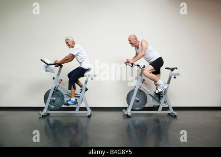 A senior woman and a mature man riding stationary bikes - Stock Photo
