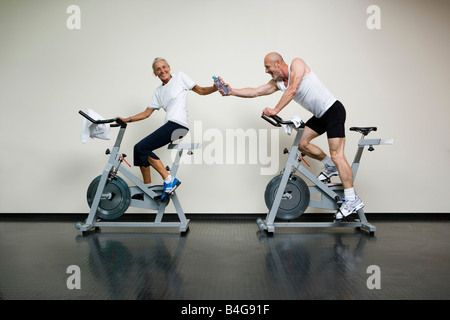 A senior woman and a mature man riding stationary bikes and passing a water bottle - Stock Photo