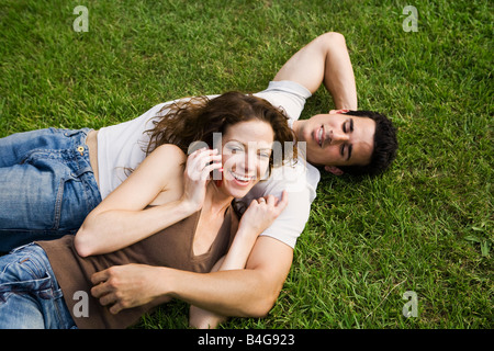A young couple snuggling on a lawn - Stock Photo