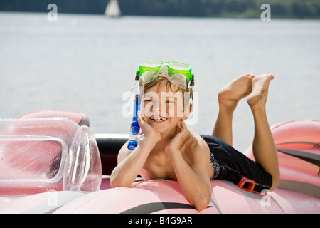 A young boy lying on an inflatable raft on a lake - Stock Photo
