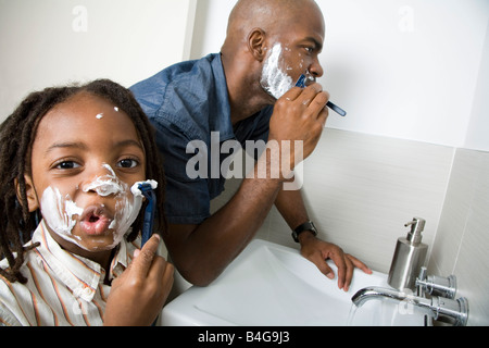 A son imitating his father shaving - Stock Photo