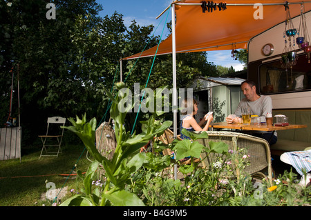 A father and daughter playing a card game outside of their caravan - Stock Photo