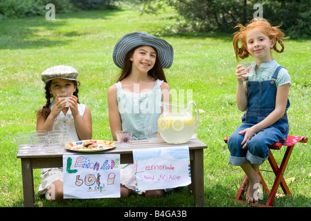 Three girls with a lemonade stand - Stock Photo