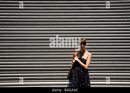 A young woman in front of metal shutter door - Stock Photo