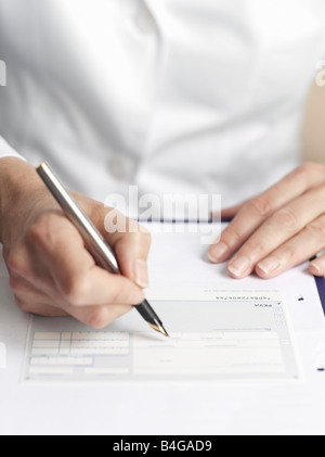 Human hands filling out medical paperwork - Stock Photo