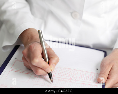 Human hands filling out a referral slip for a doctor - Stock Photo