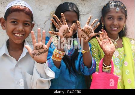 Moslem children with Eid Mubarak henna on their hands , Eid ul Fitr celebrations , India - Stock Photo