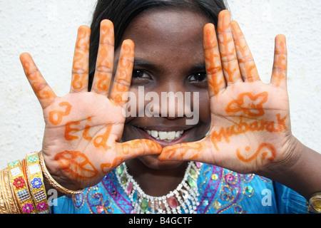 Moslem girl with Eid Mubarak henna on her hands , Eid ul Fitr celebrations , India - Stock Photo