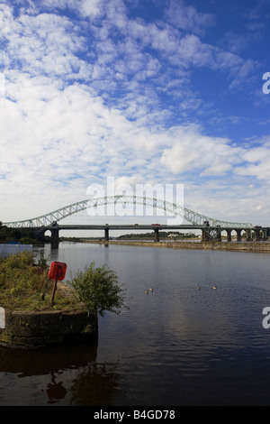 Runcorn -Widnes bridge seen from along the river with a red life-ring and a bush in the foreground and geese on - Stock Photo