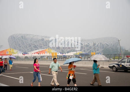 Tourists in front of the Beijing national stadium aka the Birds Nest Stadium , Beijing , China - Stock Photo