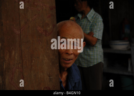 A man looks out to a buisy weekly market from the kitchen of his home in rural Gongtan Village, Chongqing Municipality, - Stock Photo
