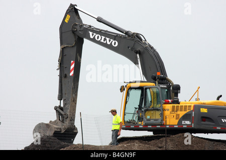 Waste Management Landfill worker on a backhoe reworking the trash in Menomonee Falls Wisconsin - Stock Photo