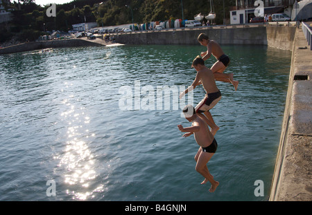 young boys jump into a harbor in the early evening - Stock Photo